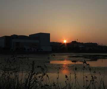 梅雨の中休みの日の出と西部市民会館(はりる)
